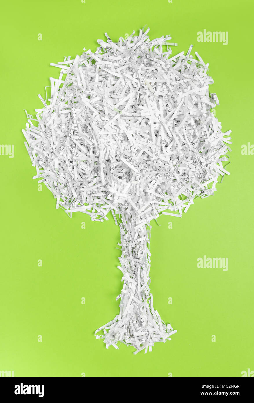 Tree made of shredded paper, on bright green background. Recycling and environment protection concept. - Stock Image
