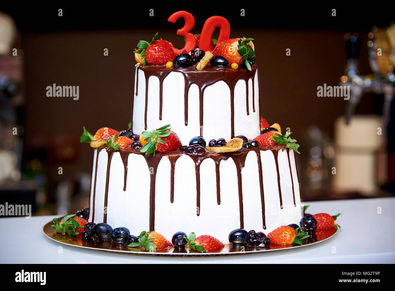 Two-tiered white cake with fresh fruits and chocolate decorated with a figure of thirty close-ups - Stock Image