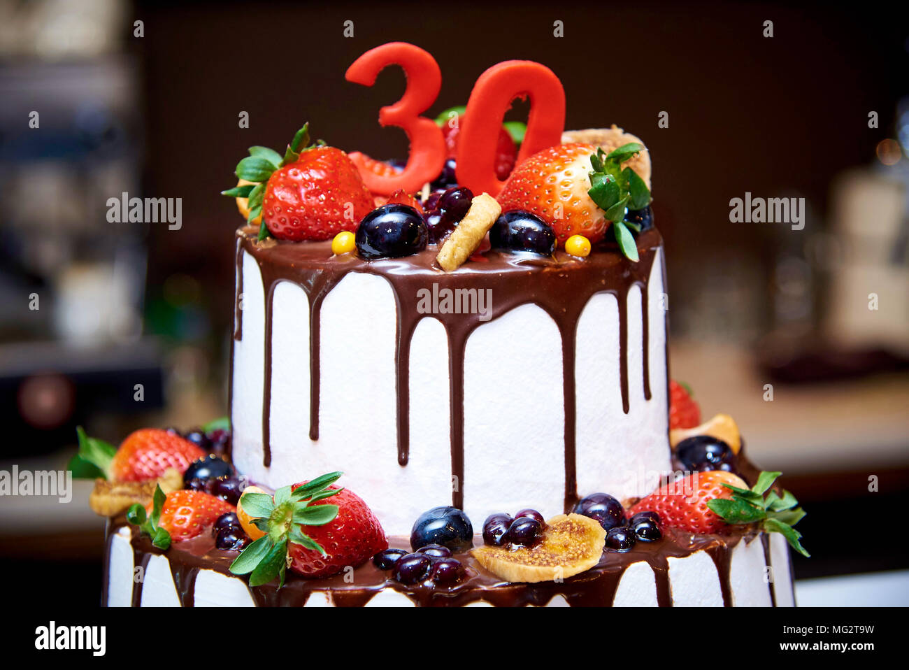 Two-tiered white cake with fresh fruits and chocolate decorated with a figure of thirty close-ups. - Stock Image