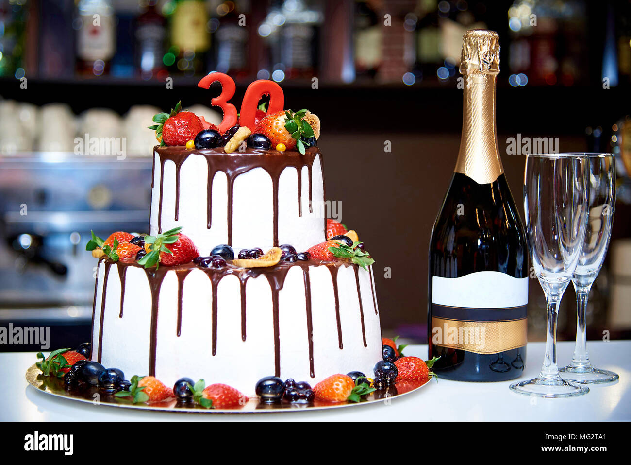 A two-tiered white cake with fresh fruit and chocolate stands next to a bottle of champagne and two bokalam on the background of a blurred bar in a re - Stock Image
