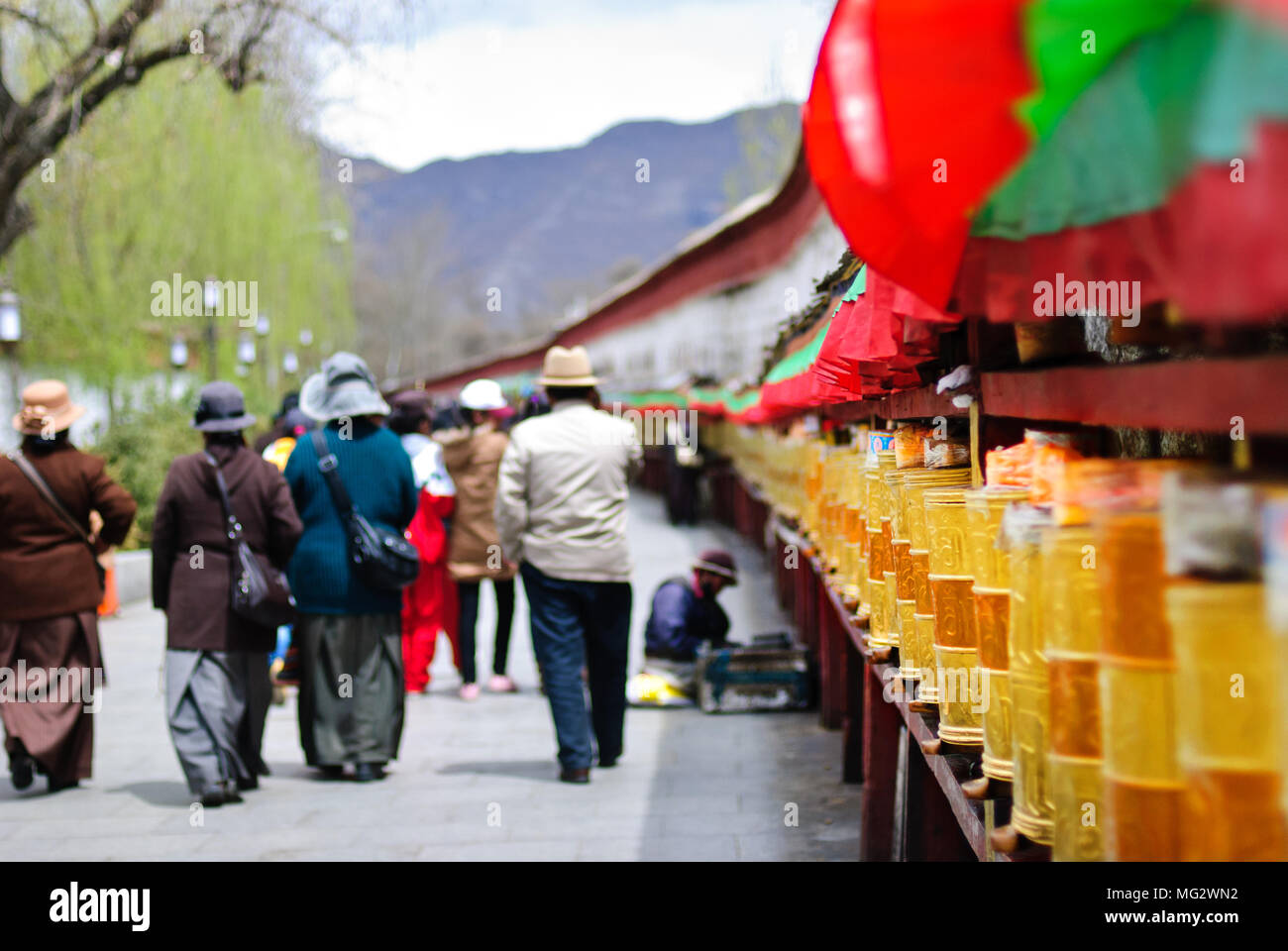 People walking near the golden prayer drums row in the street of Lhasa, Tibet background - Stock Image