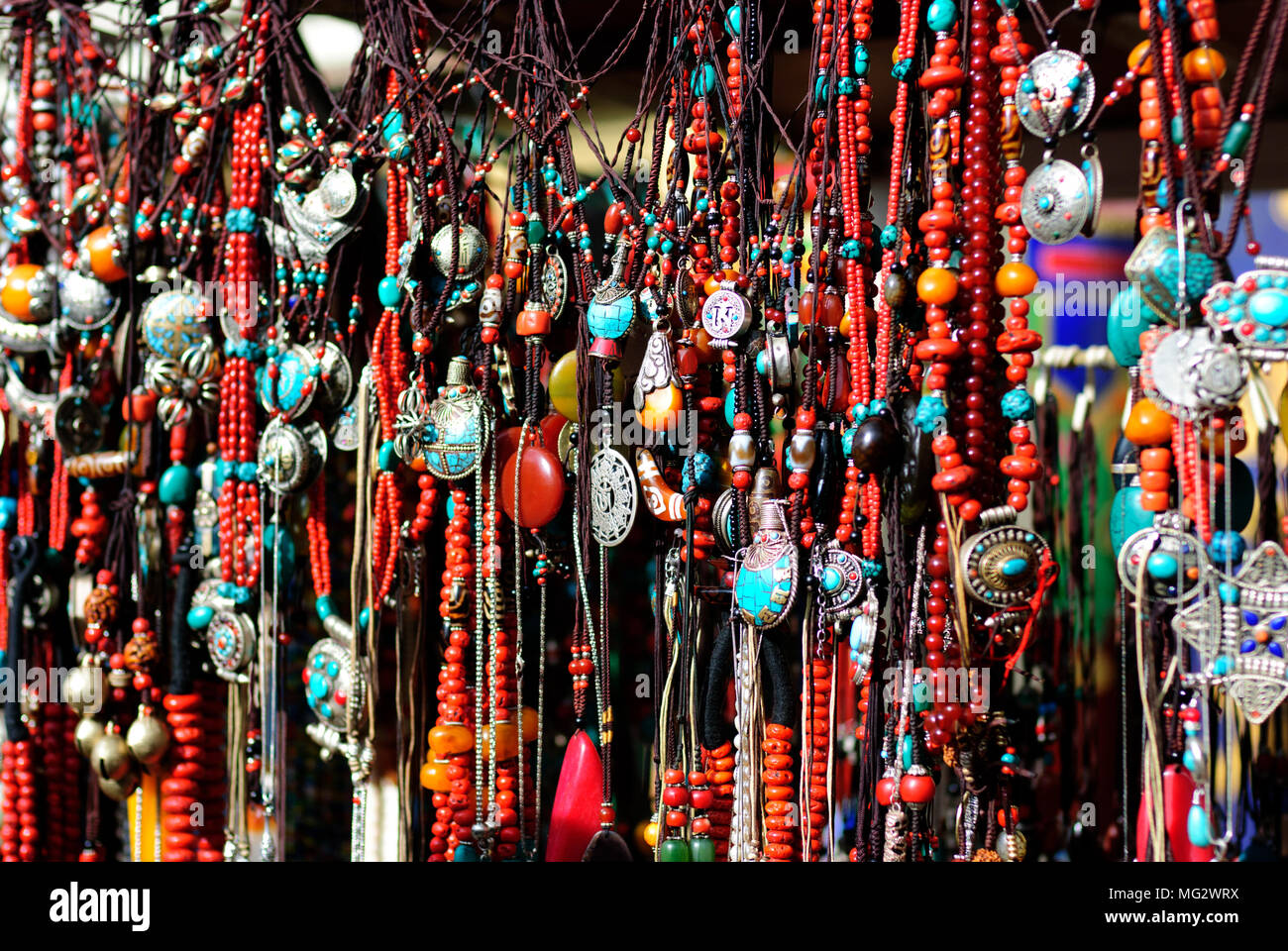Traditional decoration necklaces in Tibet market place background - Stock Image