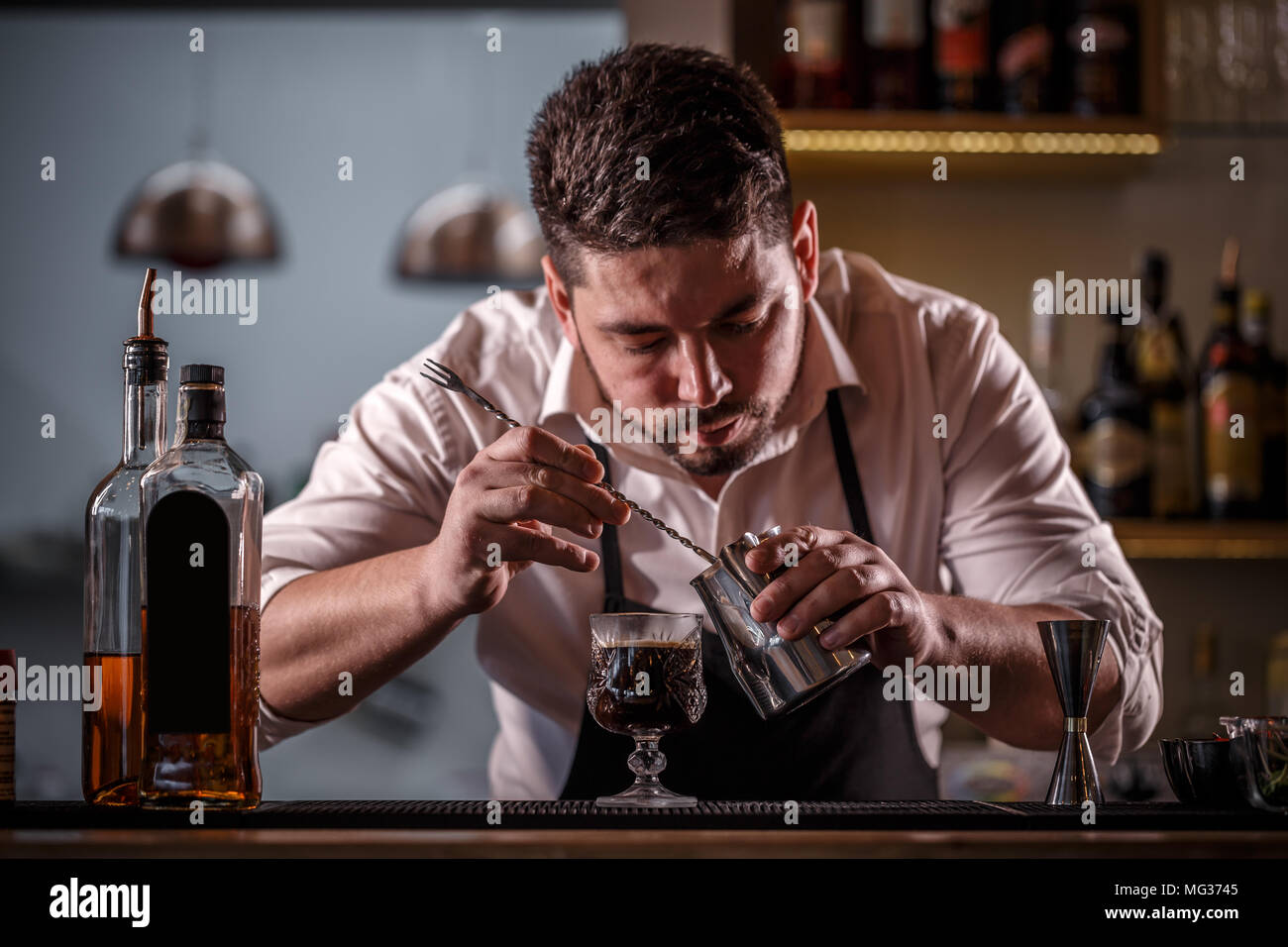 Bartender decorated coffee cocktail with milk foam - Stock Image