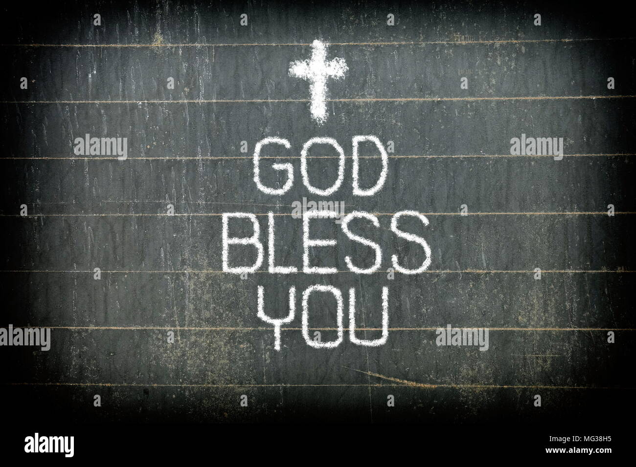 GOD BLESS YOU Chalk Writing And Little Christ Cross Sign Drawing On Old Chalkboard Background