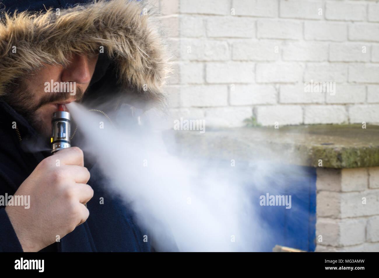 Man vaping, vape cloud with hood up - Stock Image