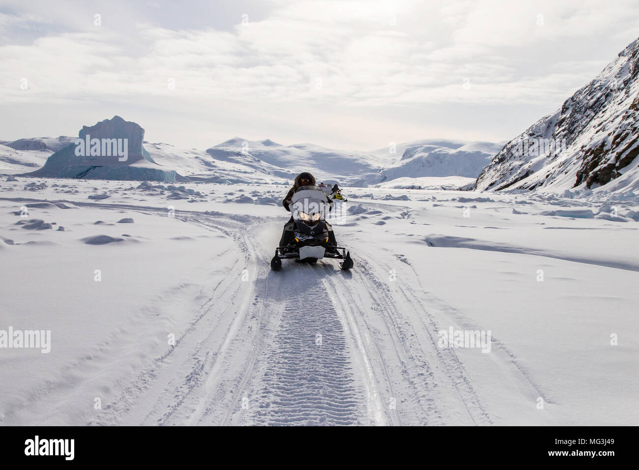 Solitary ski doo rides over a frozen fjord.  Baffin Island, Nunavut, Canada, arctic - Stock Image