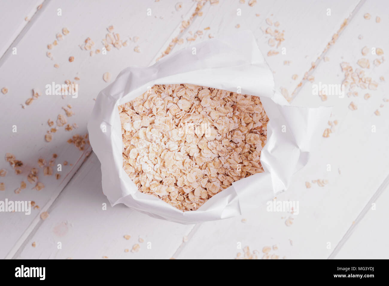 overhead view of bag of rolled oats oatmeal oat flakes on rustic white wooden table - Stock Image