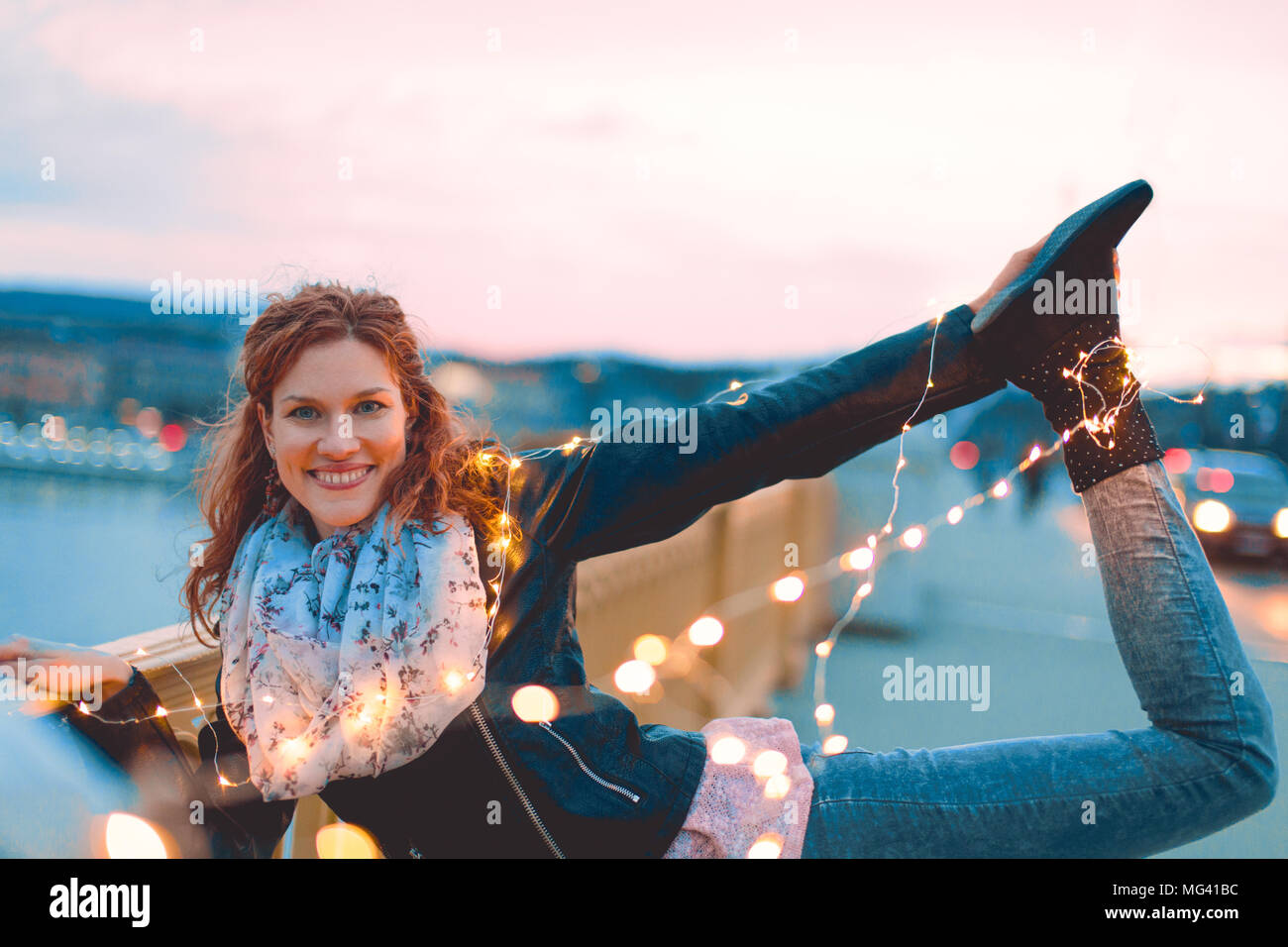 Young redhead woman posing with fairy lights outdoors and smile, teal and orange style - Stock Image