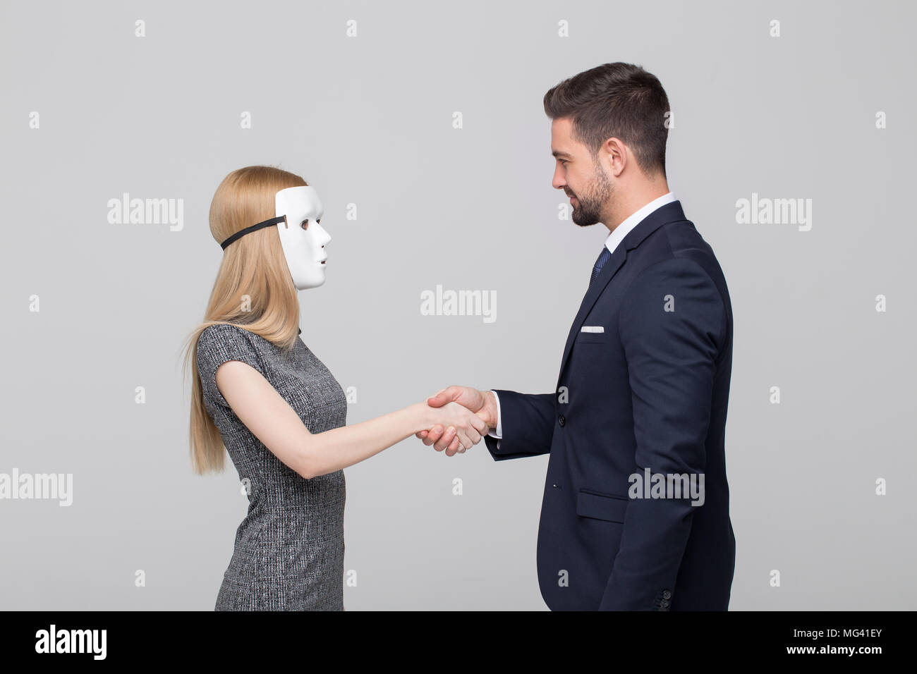 Young stylish man handshake with blonde woman in mask - Stock Image
