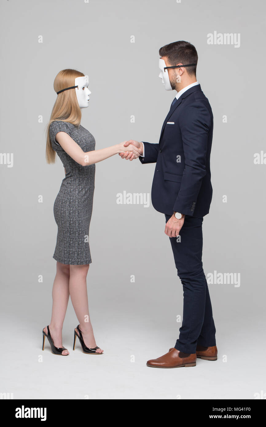 Young anonymous businesspeople in mask handshake on gray background - Stock Image