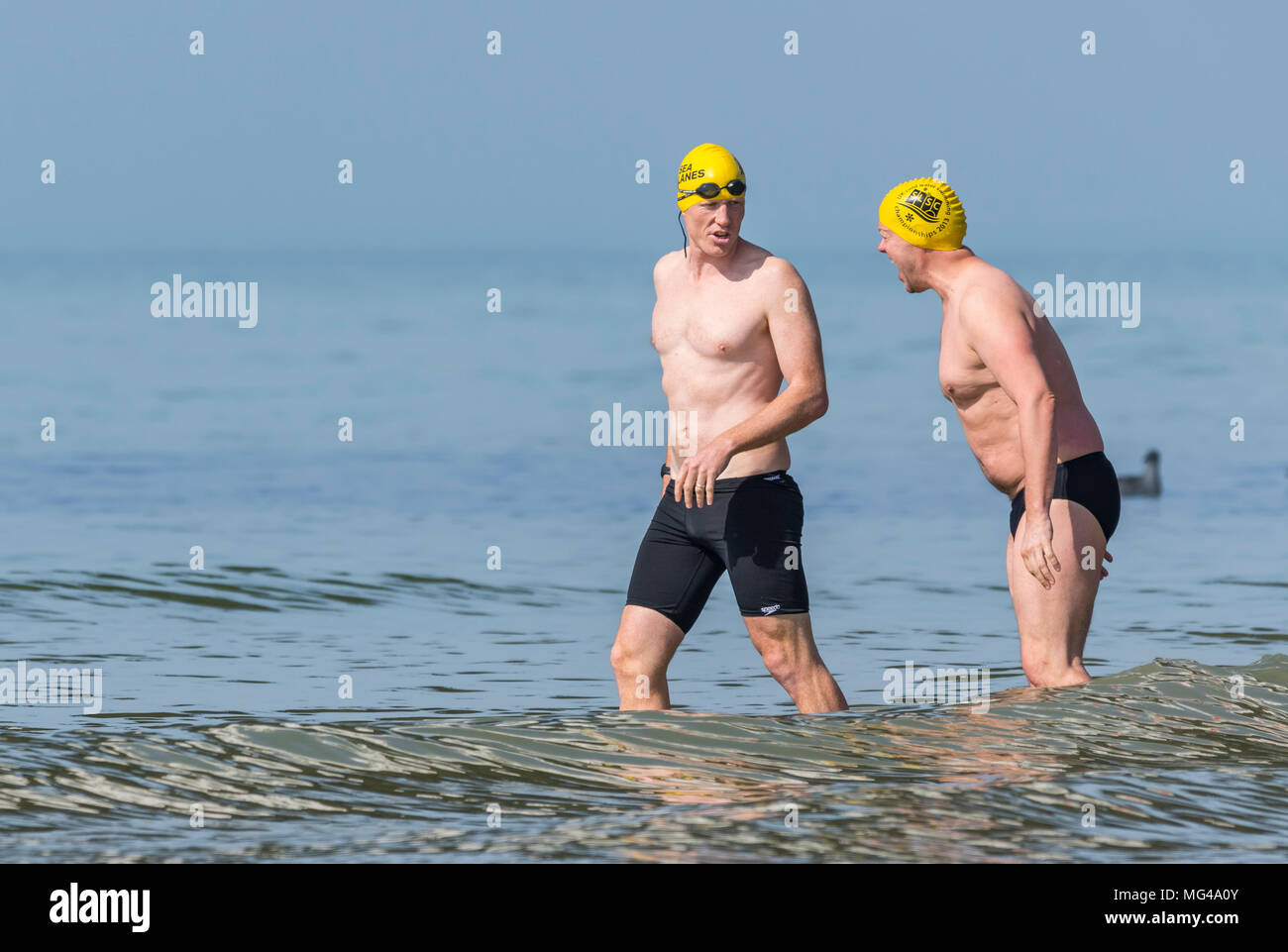 d0f58804b89 A pair of male swimmers wearing swimming caps and shorts entering the sea  on a hot
