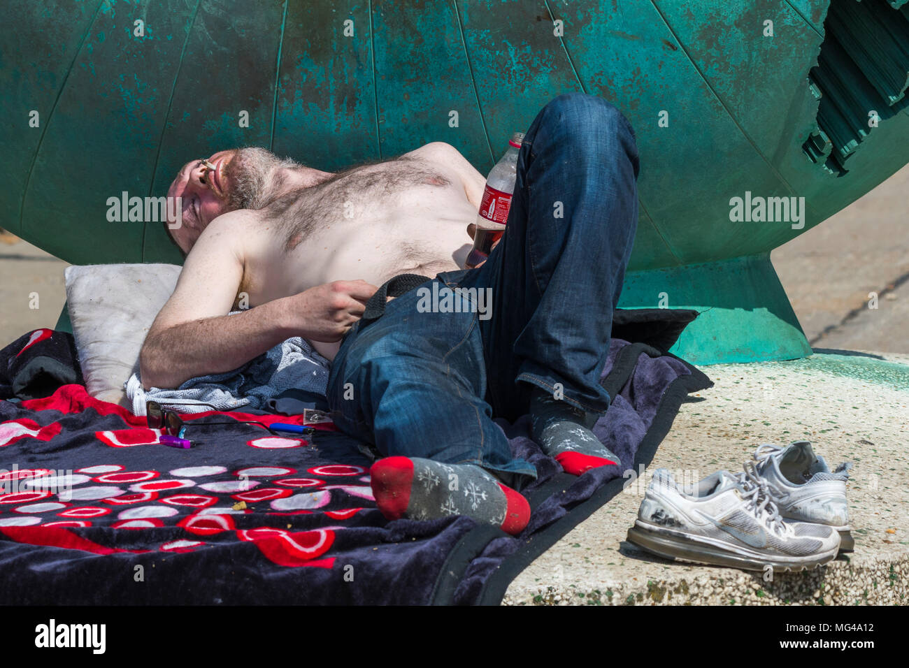 Man appearing to be homeless and sleeping rough in Brighton, East Sussex, England, UK. Homelessness UK. Down on luck. - Stock Image