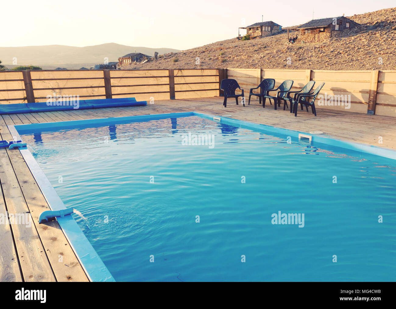 Inviting blue swimming pool in a wooden deck with plastic ...