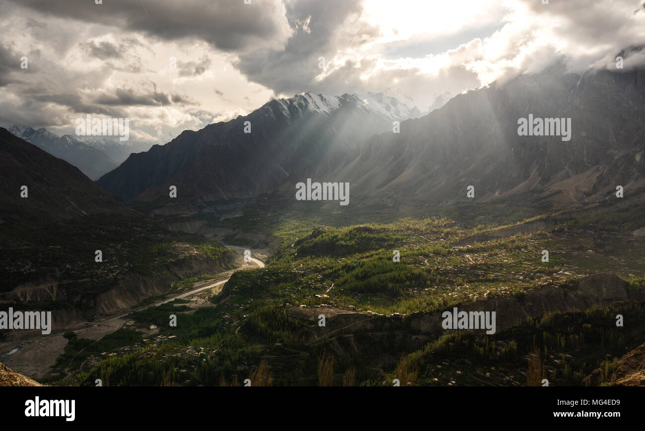 Hunza Valley Landscape, and bright sunlight through cloudy sky - Stock Image