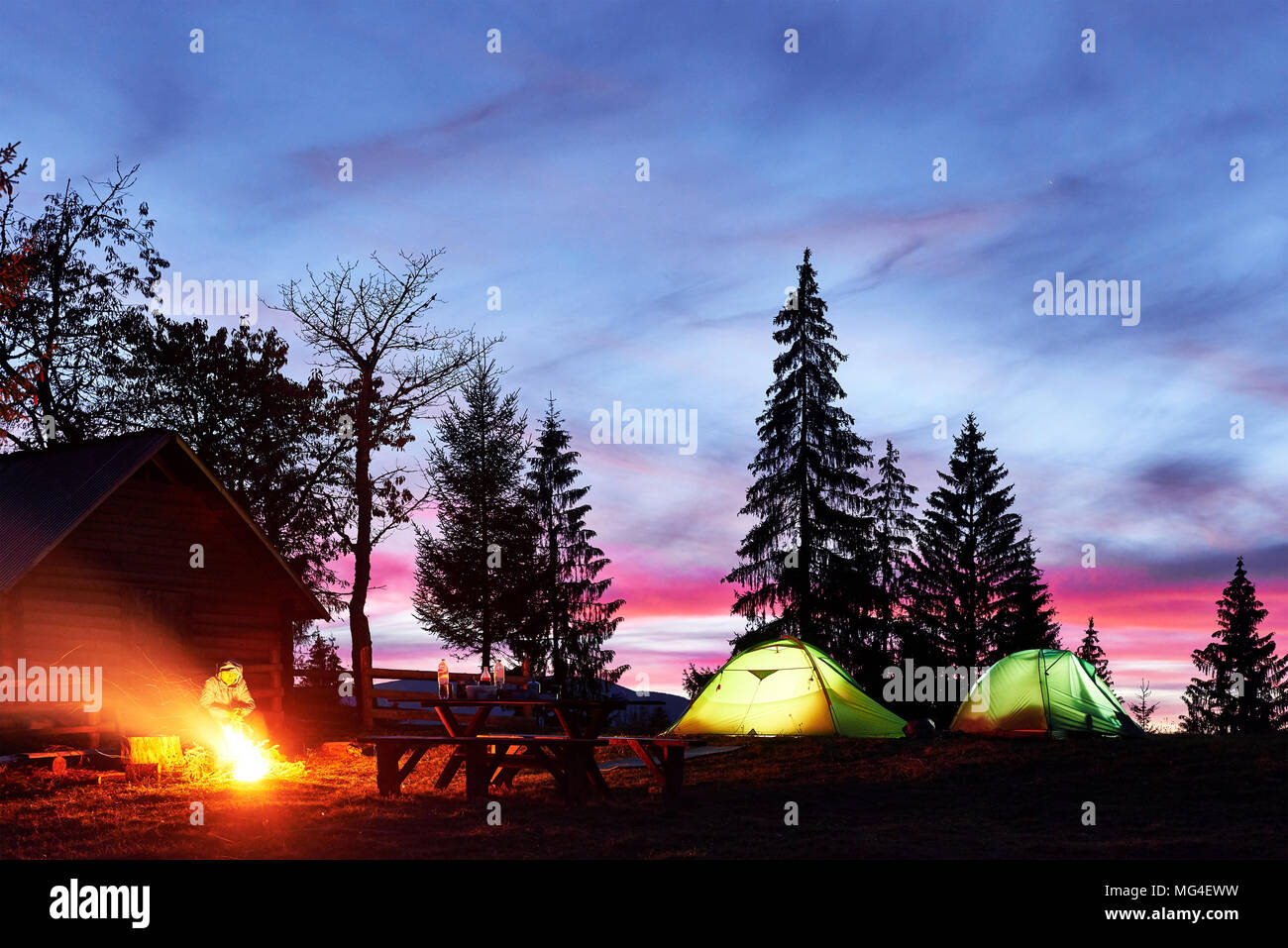 Night camping. Tourist have a rest at a campfire near illuminated tent and wooden house under amazing night sky full of stars and milky way Stock Photo