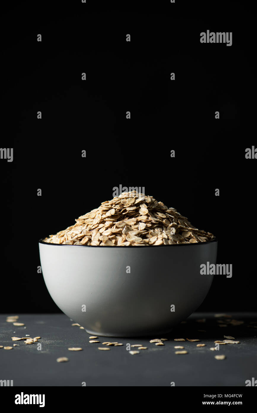 closeup of a white ceramic bowl full of rolled oats on a gray table, against a black background with some blank space on top - Stock Image