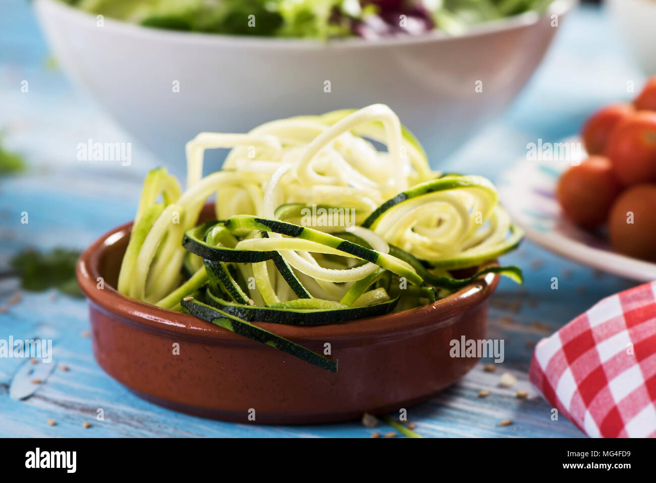 closeup of an earthenware bowl with some grated zucchini in the shape of spaghetti on a blue rustic wooden table, next to a plate with cherry tomatoes Stock Photo