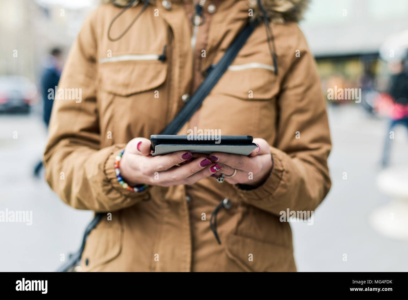 closeup of a young caucasian woman, with her fingernails painted purple, using a tablet in the street Stock Photo