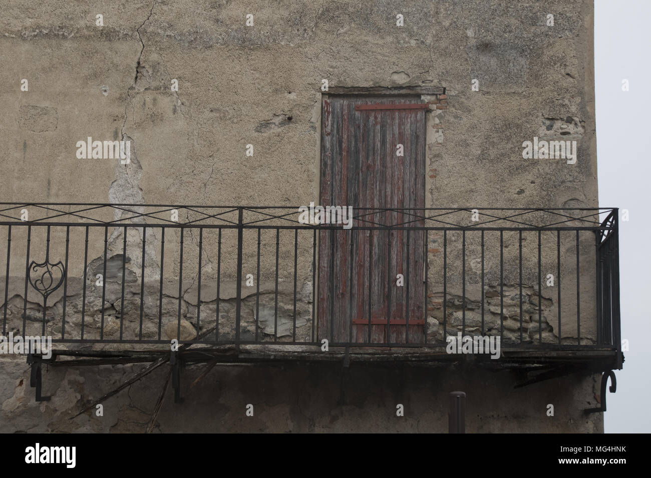First floor balcony and closed wooden door in Catllar, village near Prades, Languedoc-Roussillon, Pyrénées-Orientales, France. - Stock Image