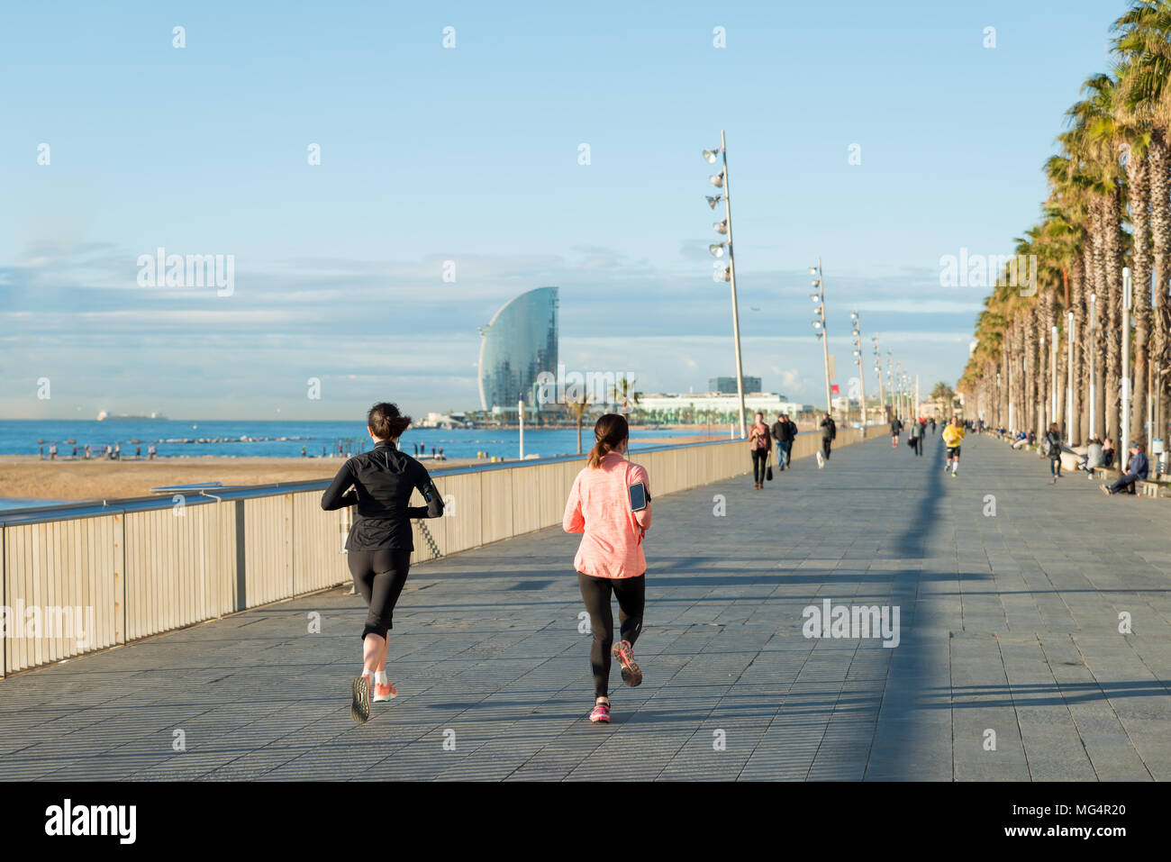 96aaf193c84a2 Running jogging on Barcelona Beach, Barceloneta. Healthy lifestyle people  runners training outside on boardwalk. Multiracial couple, Asian woma fitnes