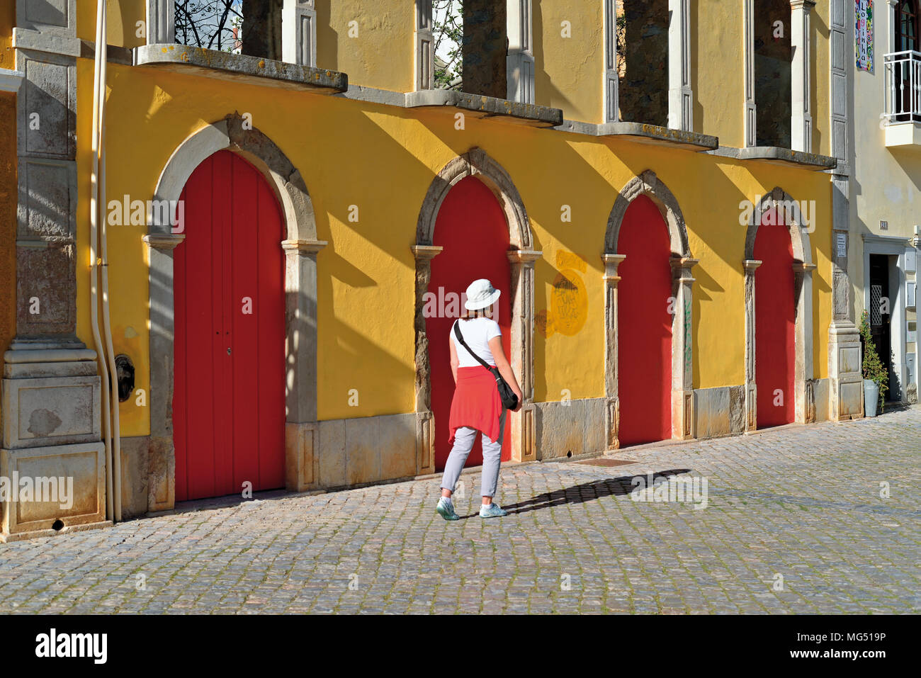 Woman passing a historic building with yellow facade and red doors - Stock Image