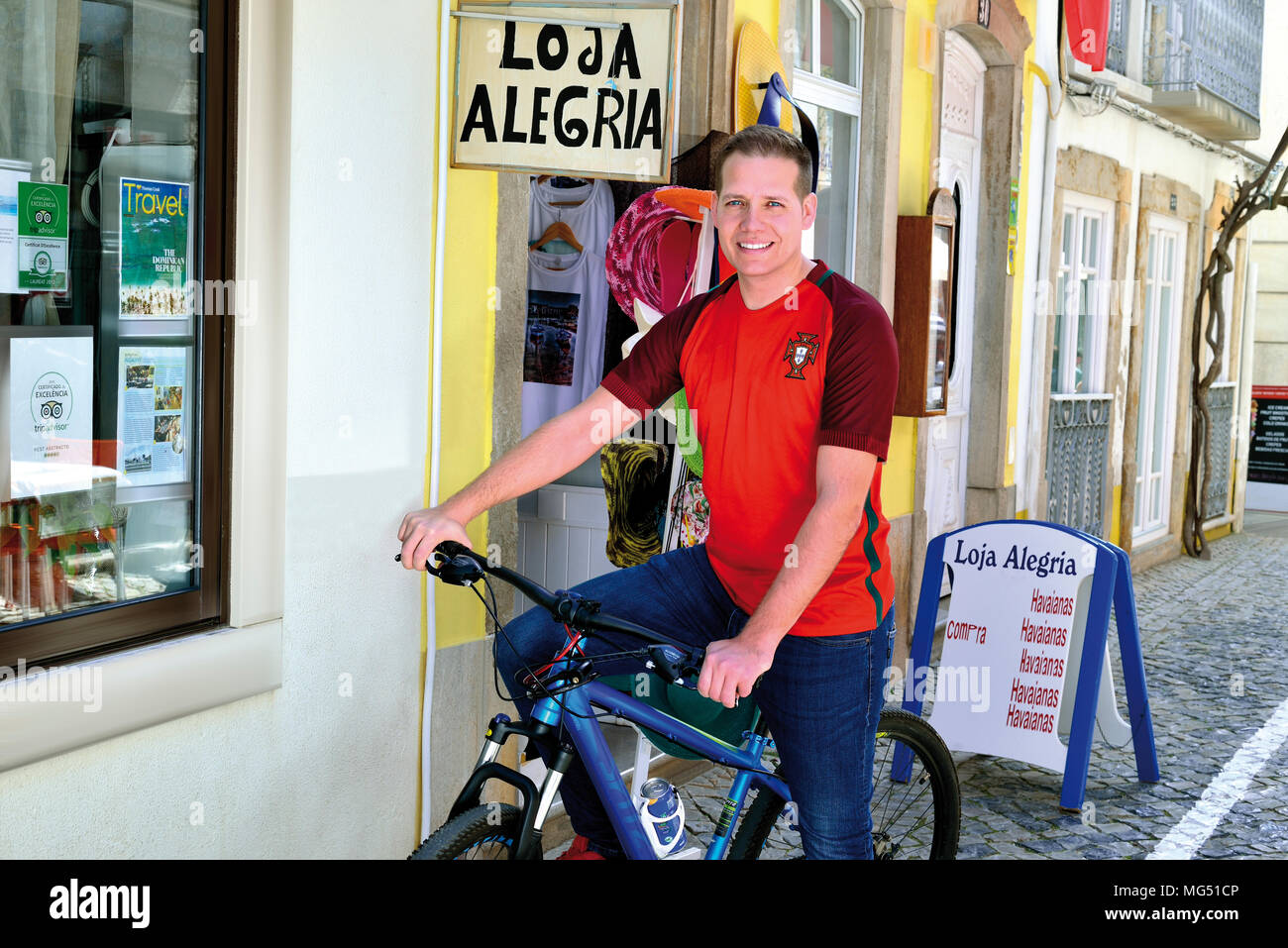 Young blond man with portuguese national  soccer team shirt sitting on a bike and smiling to the camera - Stock Image