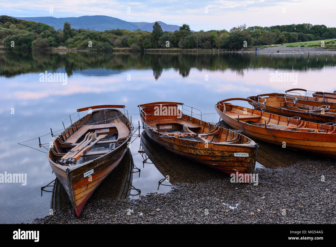 Wooden rowing boats on the shore at Keswick landing stage at dawn on Derwent Water in the Lake District National Park, Cumbria, England - Stock Image