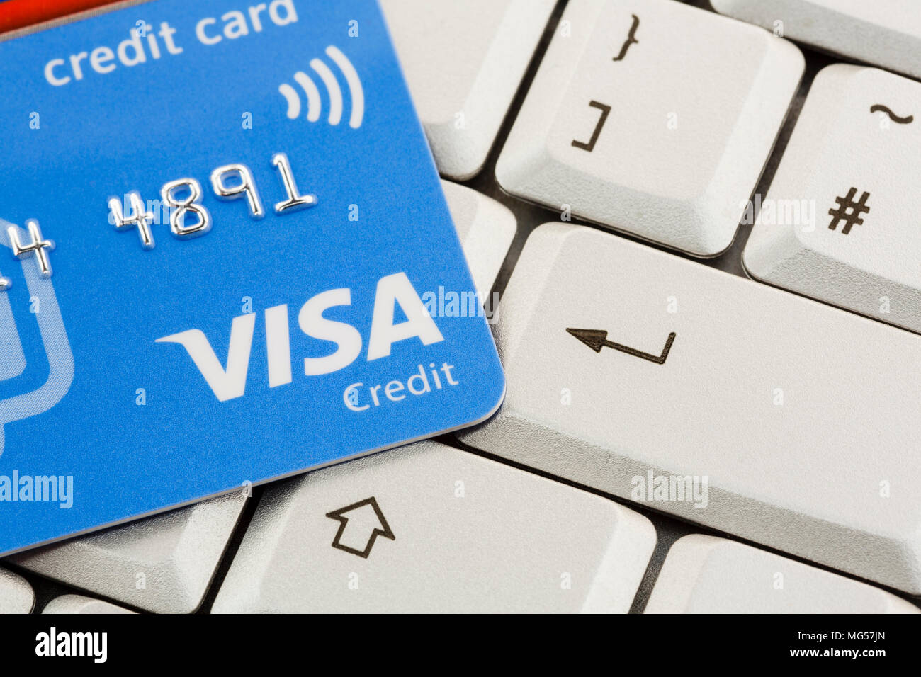 Visa card contactless credit card on a keyboard with enter key. To illustrate online internet shopping concept. England, UK, Britain - Stock Image