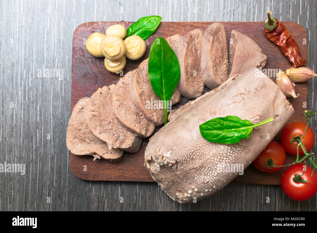 Boiled beef, pork tongue with cherry tomatoes, mushrooms, basil leaf, studio shot, isolated on wood background. Top view - Stock Image