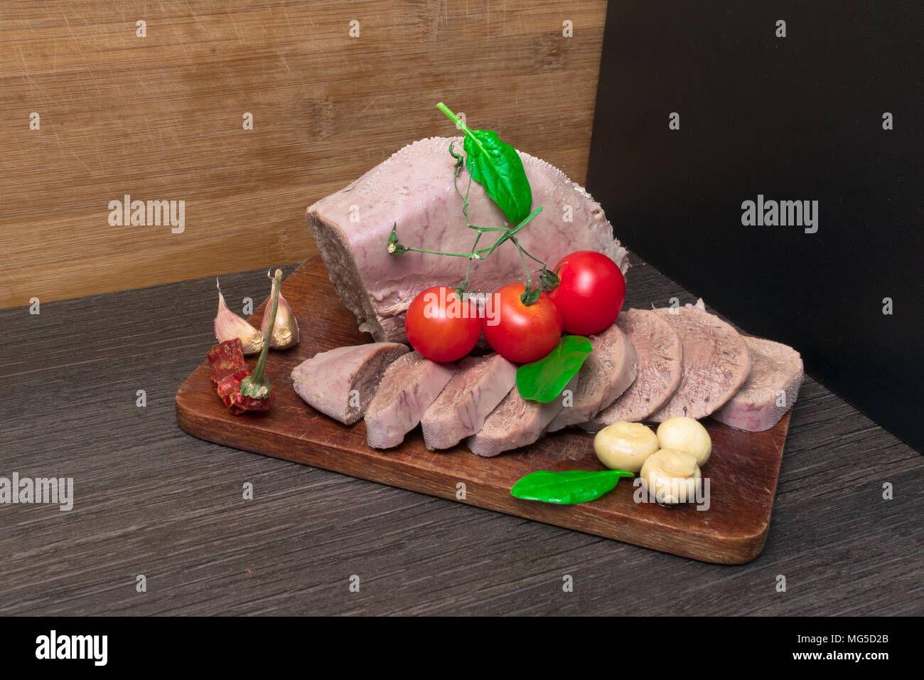 Boiled beef, pork tongue with cherry tomatoes, mushrooms -champignon, basil leaf, studio shot, isolated on wood background. Top view - Stock Image