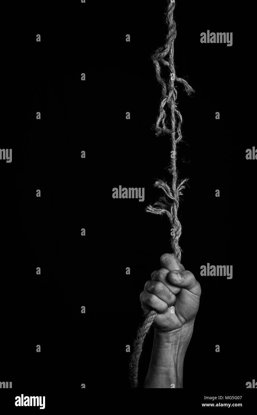 Man clings to a rope that breaks off. - Stock Image
