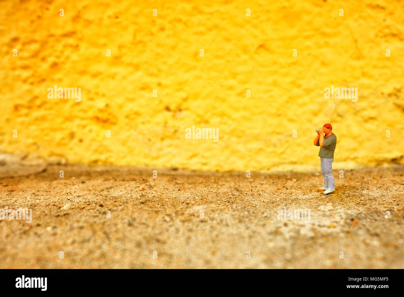 Miniature Figure Photographer with Yellow Painted Concrete Wall Background. - Stock Image