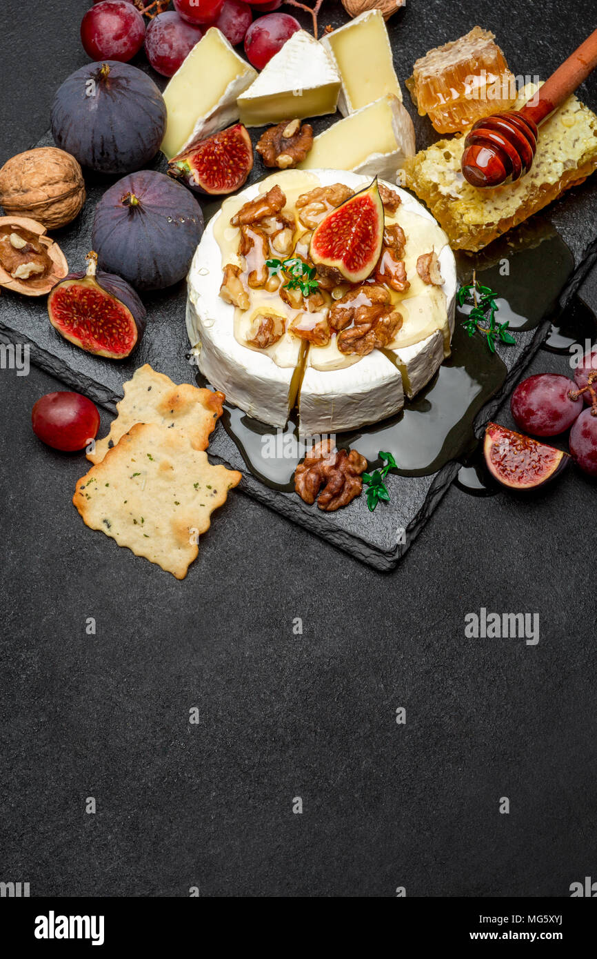Camembert cheese and walnuts on stone serving board - Stock Image