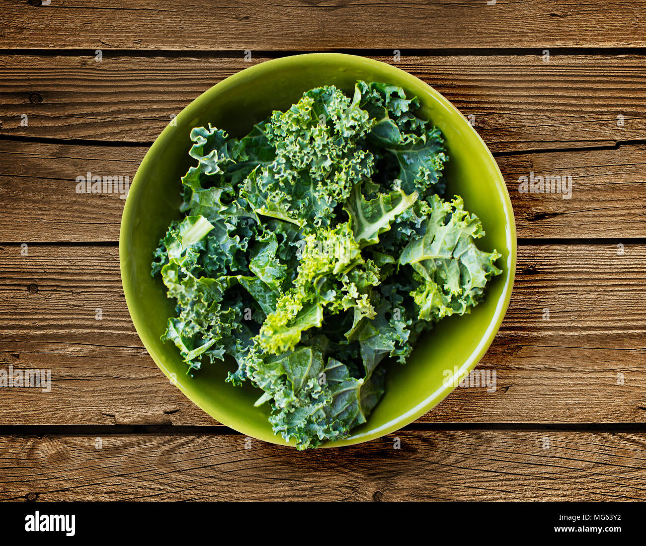 Fresh kale in a green bowl over a wooden surface - Stock Image