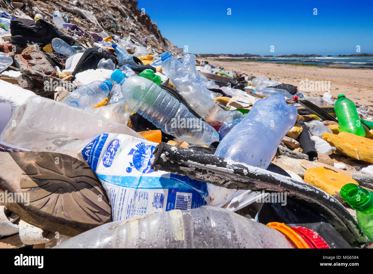 Plastic bottles and other rubbish / pollution on a beach in Morocco with sea in distance Stock Photo
