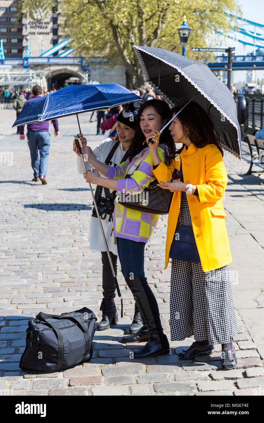 London, United Kingdom - April 23, 2015: Three ladies take a selfy while carrying parasols on a sunny London day next to the Tower of London. - Stock Image