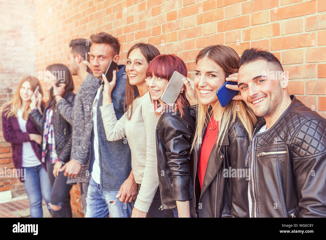 large group of friends using smart phone against a red wall of brick - Young people addicted by mobile smartphone - Technology millennials concept - Stock Image