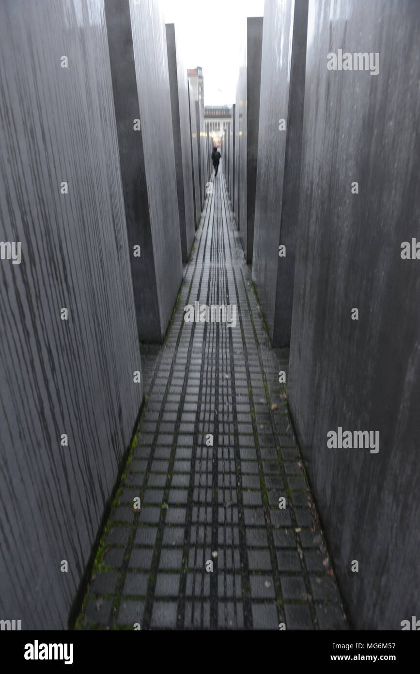 Fleeting figure moves in a blur through the Holocaust memorial Berlin Germany - Stock Image