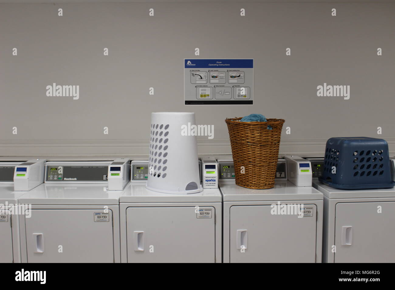 Powerful laundry machines and automatic dryers in big laundromat with a cupboard sinks for rinsing and tap water.. - Stock Image