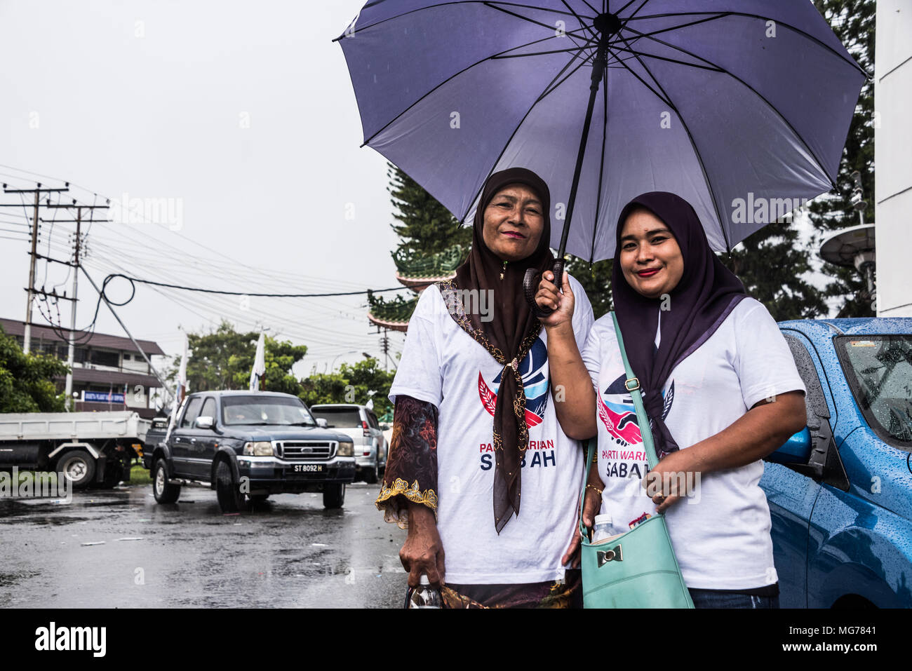 Sabah, Malaysia, 28 April 2018. Nomination Day is a washout in Semporna, but the rain doesn't stop supporters - there is no election apathy here. Semporna, Sabah, Malaysia, 28 April 2018 Credit: Elizabeth Fitt/Alamy Live News - Stock Image
