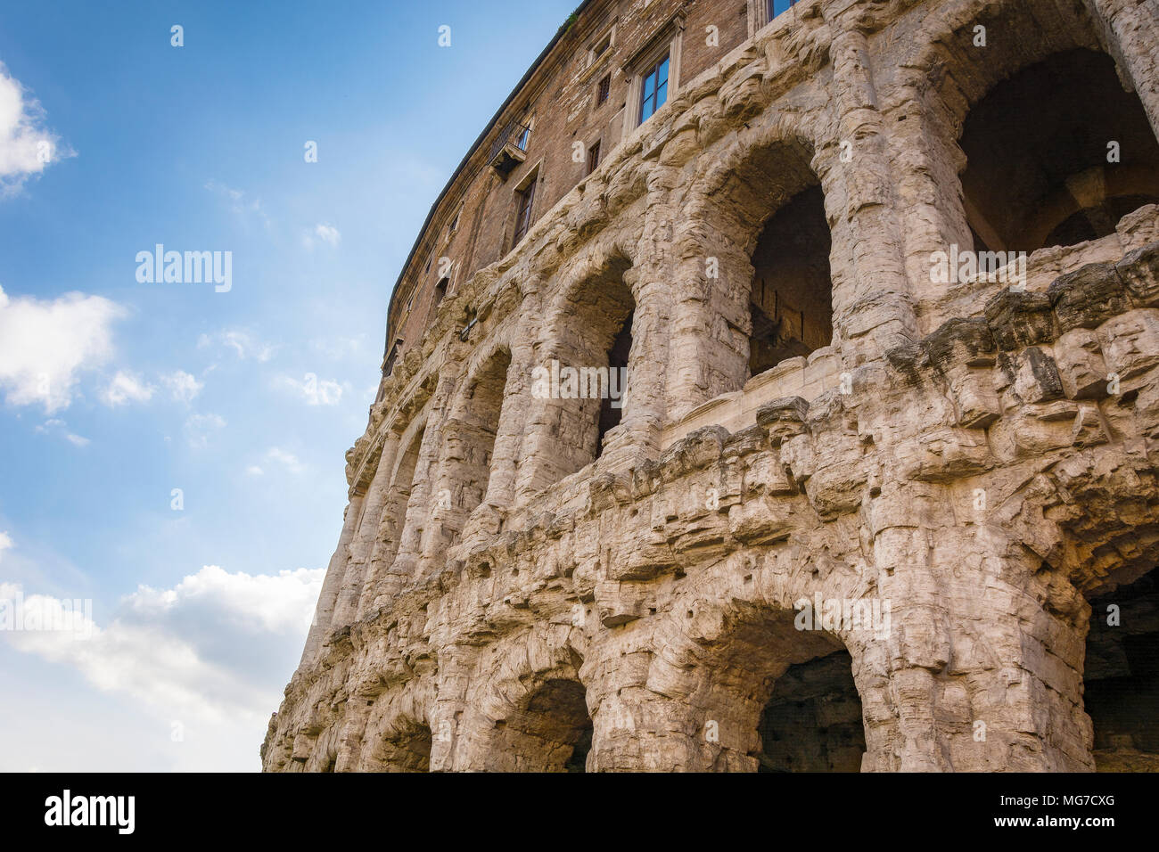 Scenic view on the ancient Theatre of Marcellus (Teatro di Marcello) and ruin of old building (antique columns and detail of the cornice) next to it o Stock Photo