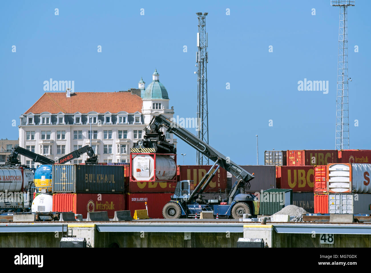 Reach stacker carrying intermodal cargo container on quay in the port of Zeebrugge / Zeebruges along the North Sea coast, West Flanders, Belgium - Stock Image