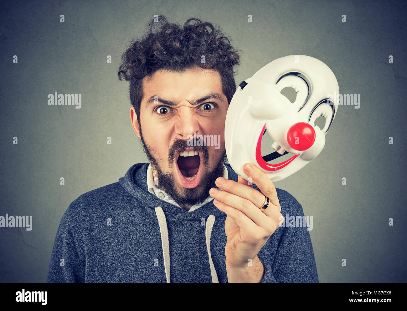 Portrait young upset angry screaming man holding a clown mask isolated on gray wall background. Human emotions feelings - Stock Image