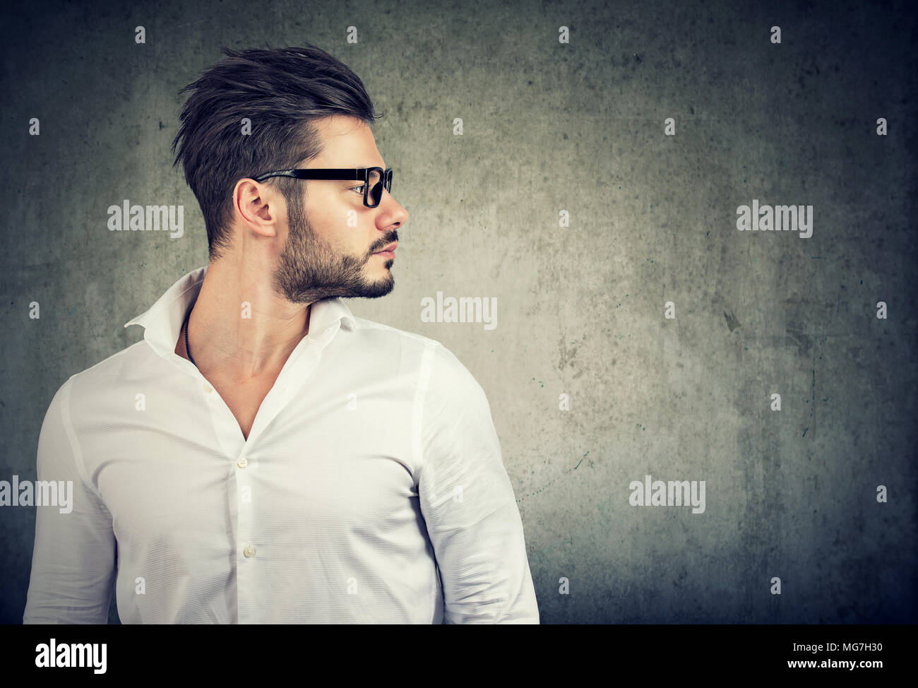 6a7c3caacdcf Stylish bearded guy with trendy hairstyle wearing glasses and white shirt  standing in profile on gray background.