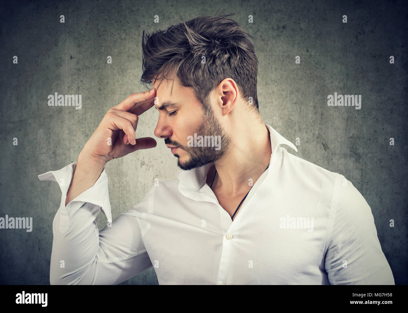 Formal man touching forehead thinking deeply and looking for solution. - Stock Image