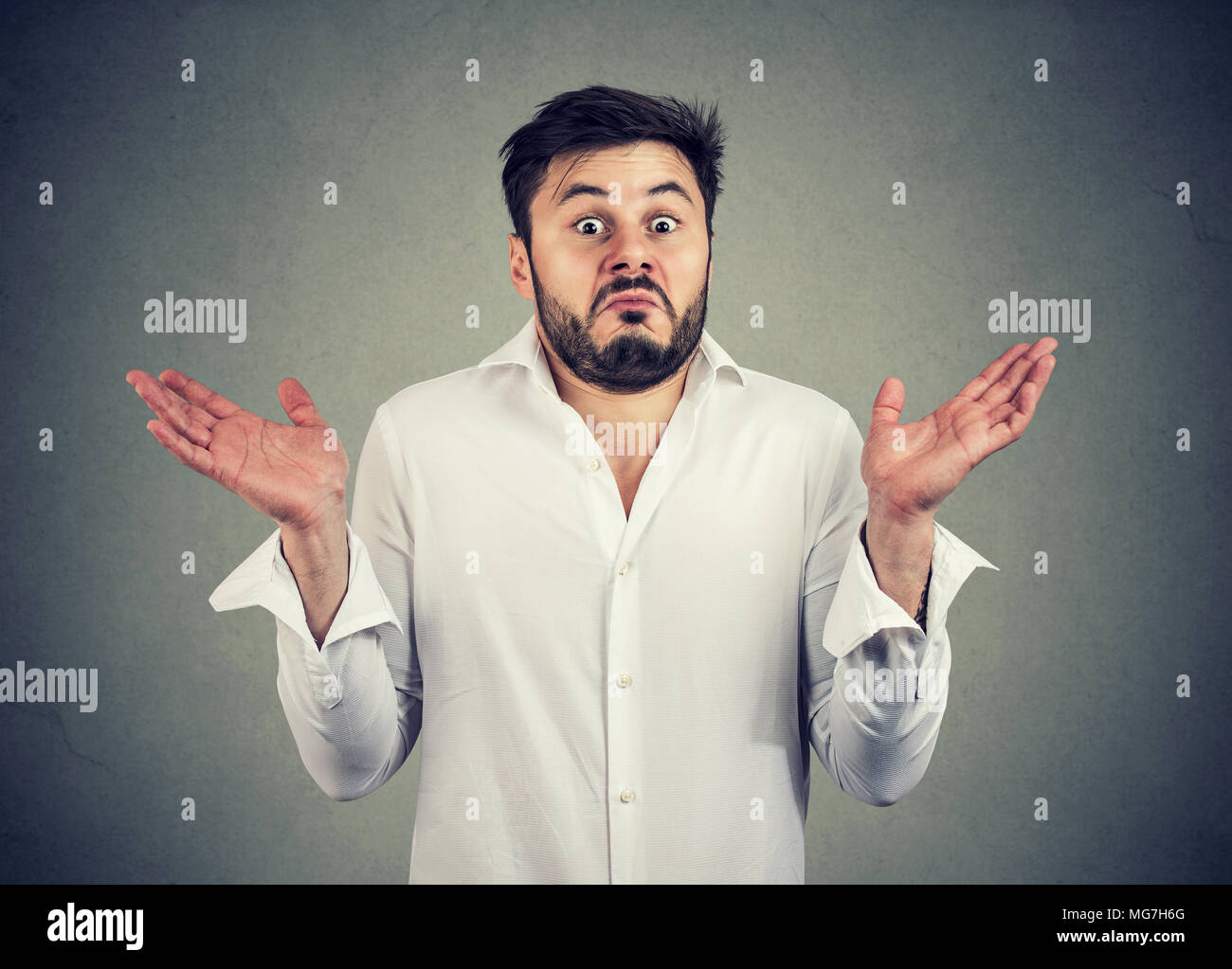 Young bearded man looking super puzzled and shrugging shoulders in question holding hands apart. - Stock Image
