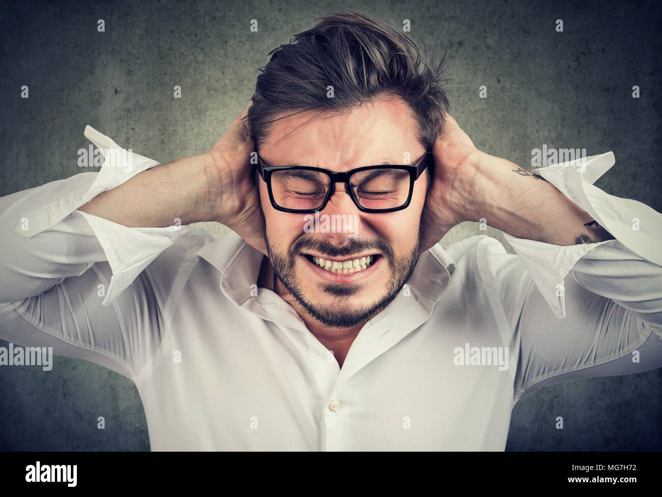 Frowning bearded man in glasses covering ears having hysteria and stress. - Stock Image