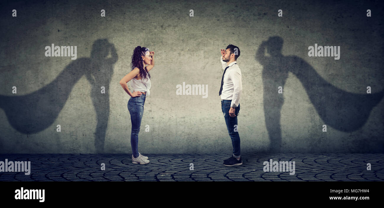 Side view of a man and woman imagining to be a super hero looking aspired. - Stock Image