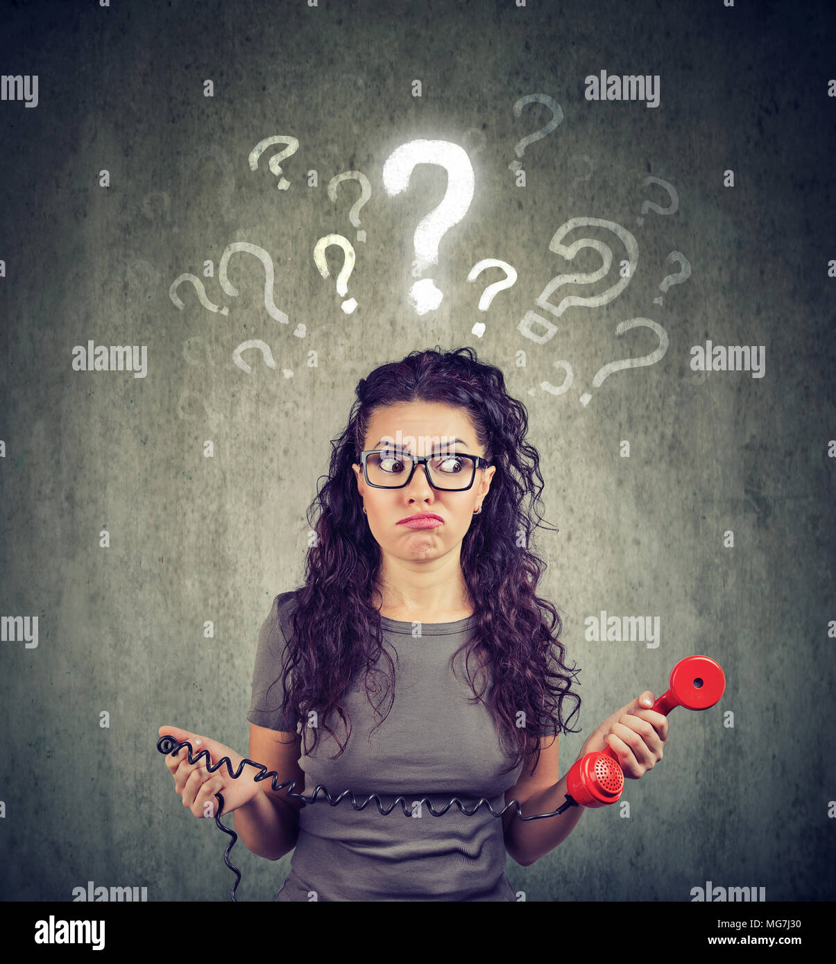 Misunderstanding and distant call. Upset worried confused woman talking on a phone has many questions isolated on gray background. - Stock Image