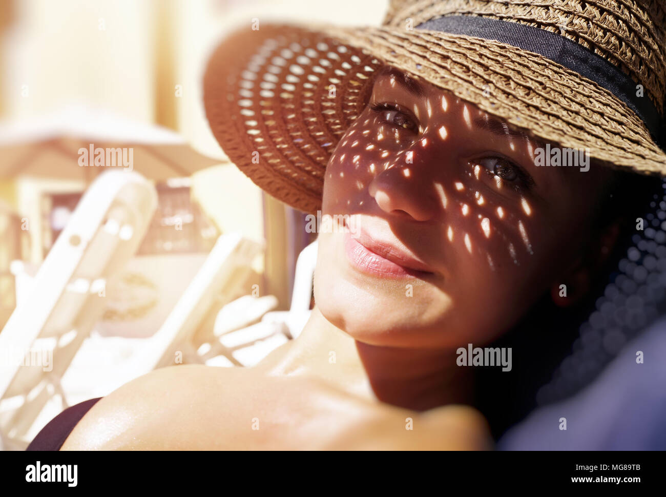 Pretty woman on the beach, closeup portrait of a nice female hides her face from the sun under a straw hat, skin protection, happy healthy summer vaca - Stock Image